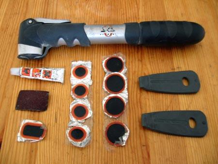 Material para arreglar un pinchazo: parches de diversos tamaños, pegamento, lija, desmontables y bomba.